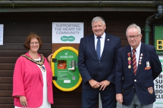 Mayor of Stratford, Cllr Victoria Alcock, with Specsavers' Paul Griffiths, and Avon Bowling Club Captain Peter Vale-Humphreys, unveiling the new defibrillator at Avon Bowls Club.